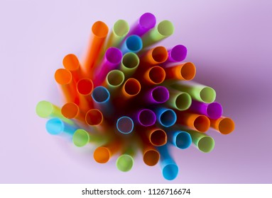 Colorful straws on a pink background