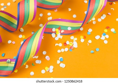 Colorful streamers and confetti on orange background, copy space