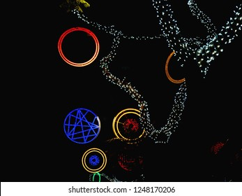 """Colorful street christmas lights on Tenerife  in """"Santa Cruz"""". Circles in red blue and gold and branches of trees which are surrounded by white fairy lights. Exemption on a black background."""