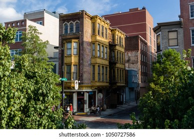Colorful street corner/old corner building with brick structures and yellow balconies standing out between the trees in the sunset light. Philadelphia, PA, United States, July 9, 2010.