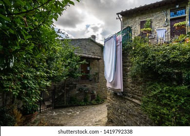 Colorful street in Cortona with bed sheets hanging on a balcony. Cortona is a beautiful medieval town in Tuscany, Italy