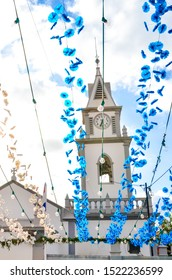 Colorful street decoration hanging on the street in front of the Roman Catholic church in Loreto, Madeira, Portugal. Portuguese religious festival decor. Paper flowers in blue and white color.