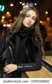 Farbiges Straßenporträt von Brunette in schwarzem Winteroutfit in der Nacht.