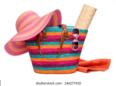 Colorful striped beach bag with a straw hat sun mat towel and sunglasses, isolated on white