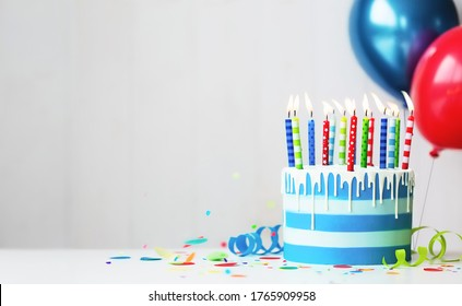 Colorful striped buttercream birthday cake with birthday candles and balloons