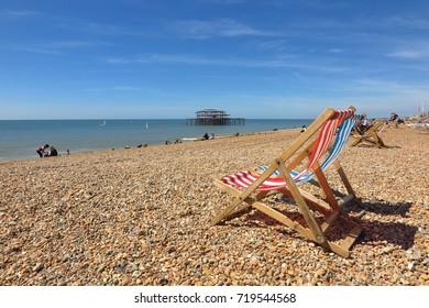 Colorful striped deck chairs on pebble beach in Brighton, England, UK. Windsurfers explore the sea around Brighton West Pier.