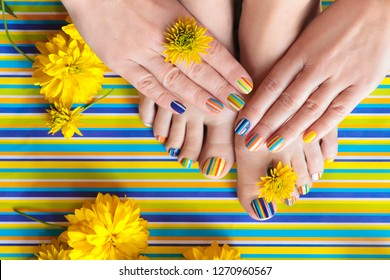 Colorful striped fashion summer pedicures and manicures for women's short nails with yellow flowers.Nail art.