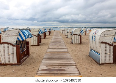 Colorful striped wooden hooded beach chairs (strandkorb) on a sandy Baltic beach in Travemunde seaside resort near Luebeck city, Germany