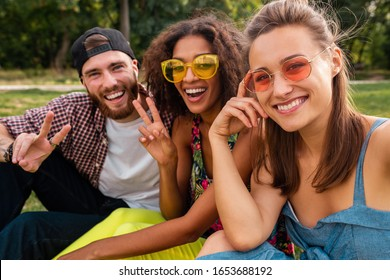 colorful stylish happy young company of friends sitting park, man and women having fun together, summer hipster fashion style, traveling with camera, taking selfie pictures, smiling and positive