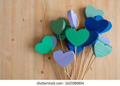 Colorful Styrofoam Hearts on sticks on a Wooden Background