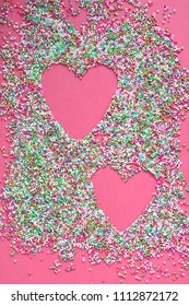 colorful sugar pearls and shape of a heart on pink background