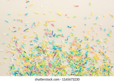 Colorful sugar sprinkles used for delicious dessert. Sprinkles on white background with copy text space