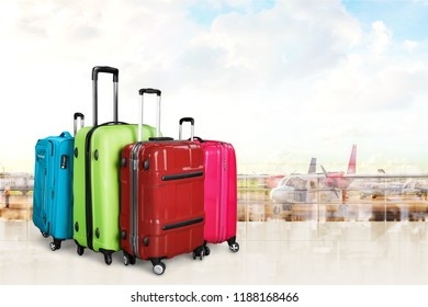 Colorful suitcases and backpack on wall background