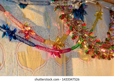 Colorful Sukkah decoration shiny garland at sunset light.