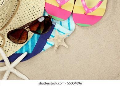 Colorful summer beachwear, flip flops, towel, hat, sunglasses and starfish on sand beach.