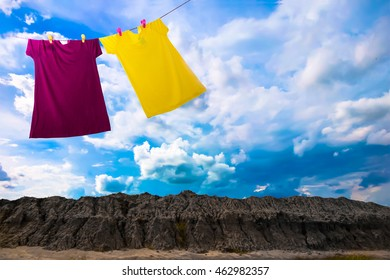 Colorful a summer clothes hang on a soil mountain on blue sky.