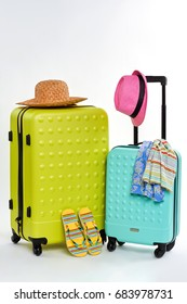 Colorful summer clothes and suitcases. Bright elements of summer holiday.