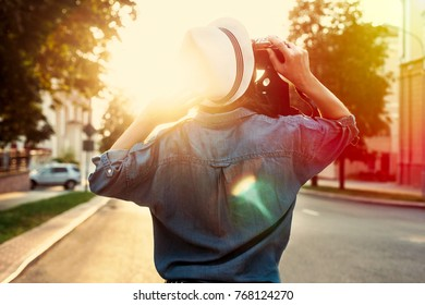 Colorful summer evening portrait of young woman having fun on the street in hat. Back view.