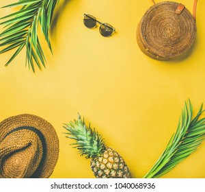 Colorful summer female fashion outfit flat-lay. Straw sunhat, bamboo bag, sunglasses, palm branches and pineapple over yellow background, top view, copy space. Summer fashion or holiday travel concept