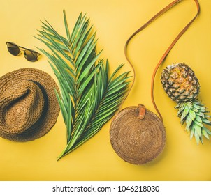 Colorful summer female fashion outfit flat-lay. Straw sunhat, bamboo bag, sunglasses, palm branches and pineapple over yellow background, top view. Summer vacation fashion or travel concept