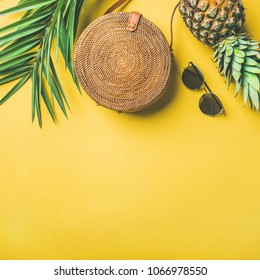 Colorful summer female fashion outfit flat-lay. Straw hat, bamboo bag, sunglasses, palm branches, pineapple over yellow background, top view, copy space, square crop. Summer fashion, holiday concept