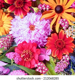 Colorful summer flower background with a closely packed bouquet of assorted blooms including dahlias and vivid Gerbera daisies in square format for a festive occasion