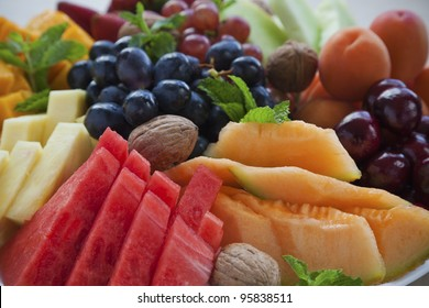 Colorful summer fruit platter with watermelon, cantaloupe, grapes, cherries, apricots, walnuts and mint