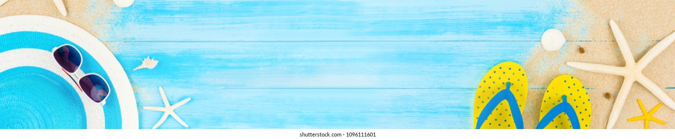 Colorful summer holiday beach background with accessories on light blue wood panel, horizontal web banner background