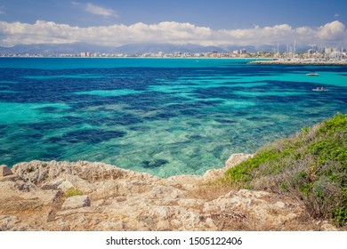 Colorful summer landscape with bay, boat, rocks, blue water, sky. Balearic islands Mallorca. View on Palma de Mallorca