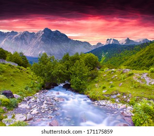 Colorful summer landscape near the river in the huge mountains. Sunset