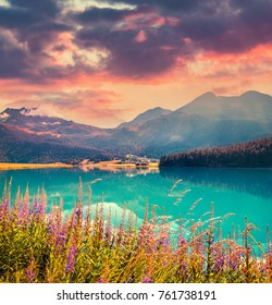 Colorful summer morning on the Champferersee lake. Impressive sunrise view of Silvaplana village in the morning mist. Alps, Switzerland, Europe. Beauty of countryside concept background.