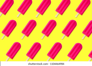 Colorful summer pattern. Bold pink popsicles on a bright yellow background. Top view.