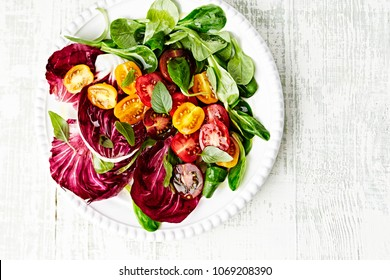Colorful Summer Salad with Cherry Tomatoes, Radicchio Corn Salad, Baby Spinach and fresh Basil. Concept for a tasty and healthy vegetarian meal. Top view. Copy space.