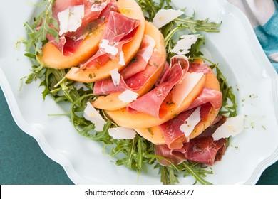 Colorful summer salad with fresh cantaloupe and Serrano ham