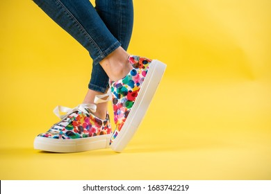 Colorful summer shoes sneackers with young woman and blue jeans on yellow background