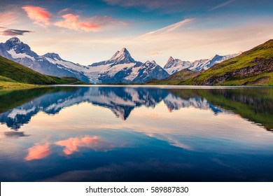 Colorful summer sunrise on Bachalpsee lake with Schreckhorn and Wetterhorn peaks on background. Picturesque morning scene in the Swiss Bernese Alps, Switzerland, Europe.