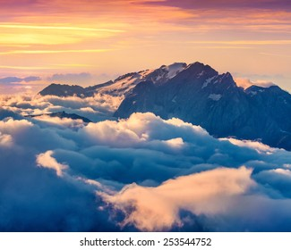 Colorful summer sunrise on the foggy Val di Fassa valley with passo Sella. National Park. Dolomites, South Tyrol. Location Canazei, Campitello, Mazzin. Italy, Europe.