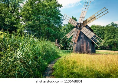 Colorful summer view of traditional romanian windmill. Sunny rural scene of Transylvania, Romania, Europe. Beauty of countryside concept background.