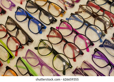 Colorful sunglasses shop with white fur background and apparel, different styles.