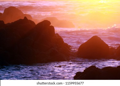 Colorful sunrays on ocean waves and rocks, background with copy space