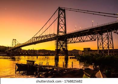 Colorful sunrise behind the Hercílio Luz bridge in Florianópolis.