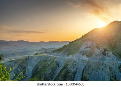 Colorful sunrise behind mountain peak with yellow sky and road stretching around mountains, natural morning landscape in Xinjiang of China