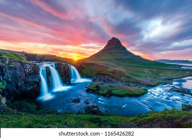 Colorful sunrise on Kirkjufellsfoss waterfall. Amazing morning scene near Kirkjufell volkano, Iceland, Europe.