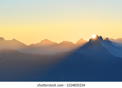 Colorful sunrise over the mountains in the Allgaeu Alps at the border region of Germany and Austria. Silhouettes of mountain ranges with yellow sky. Zugspitze in the background. Copy space.