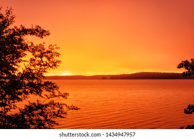 Colorful sunrise over the riverbank. The solar disk is not yet visible, but the sky and the water are already painted yellow and orange.