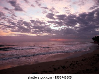 Colorful sunrise over a tropical ocean view. Moody dreamy tones with dark and bright clouds with a blue sky behind.