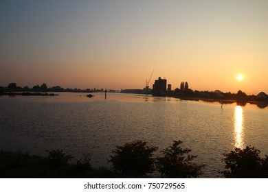Colorful sunrise reflection in the water of the River Hollandse IJssel in the Netherlands