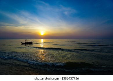 Colorful Sunrise with Sand and boat on the ocean at Huahin Thailand .