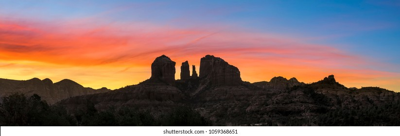 A colorful sunrise sky silhouettes Cathedral Rock and the surrounding rugged landscape of Sedona, Arizona.
