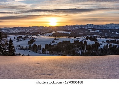 Colorful sunrise with some clouds over the Allgaeu Alps (Bavaria, Germany) in winter. Vibrant snow cover. Rocky mountains in the background.